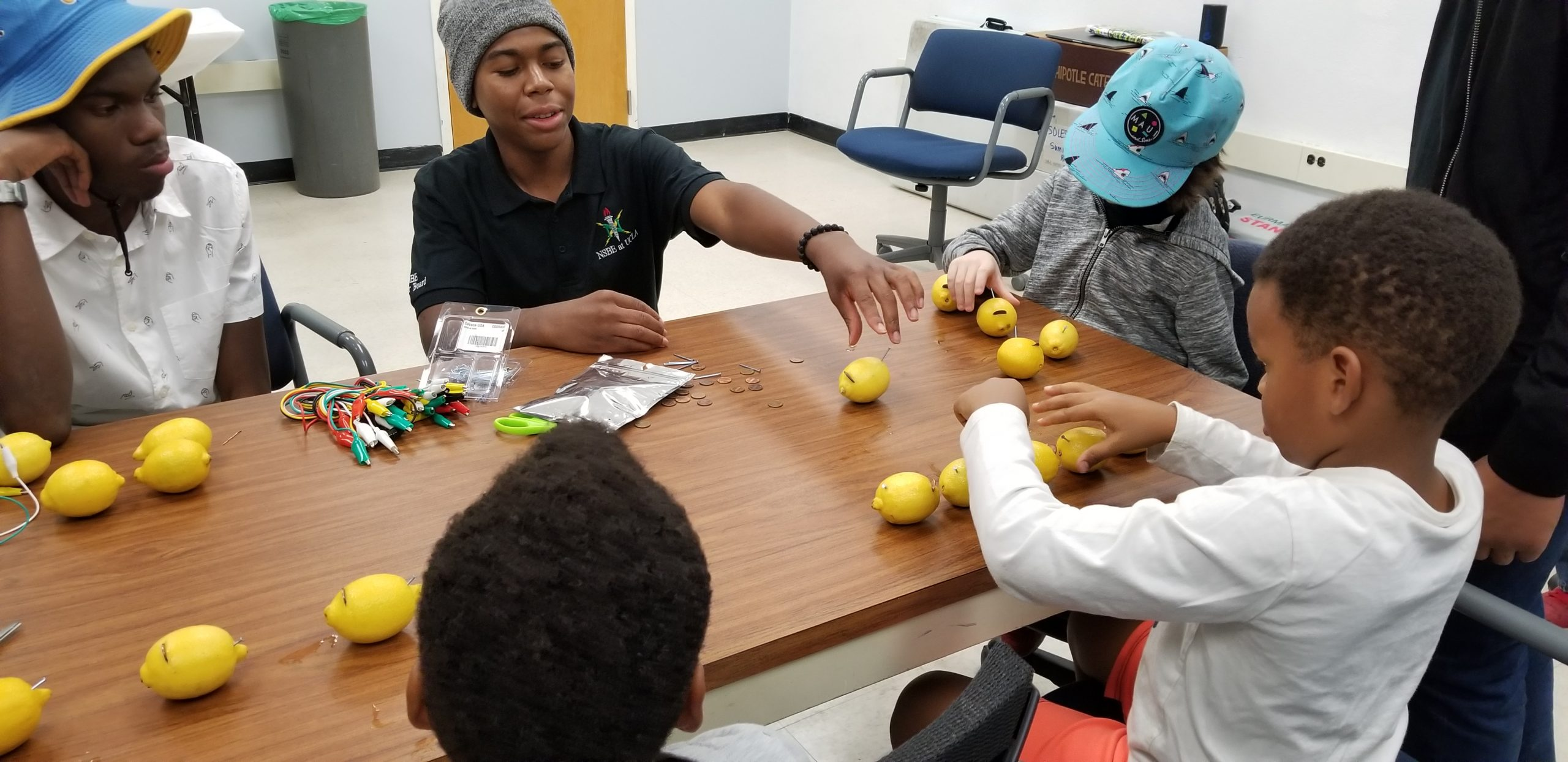 NSBE members Michael Buck and Emmanuel Boitey assist visiting homeschoolers in assembling batteries made of lemons.