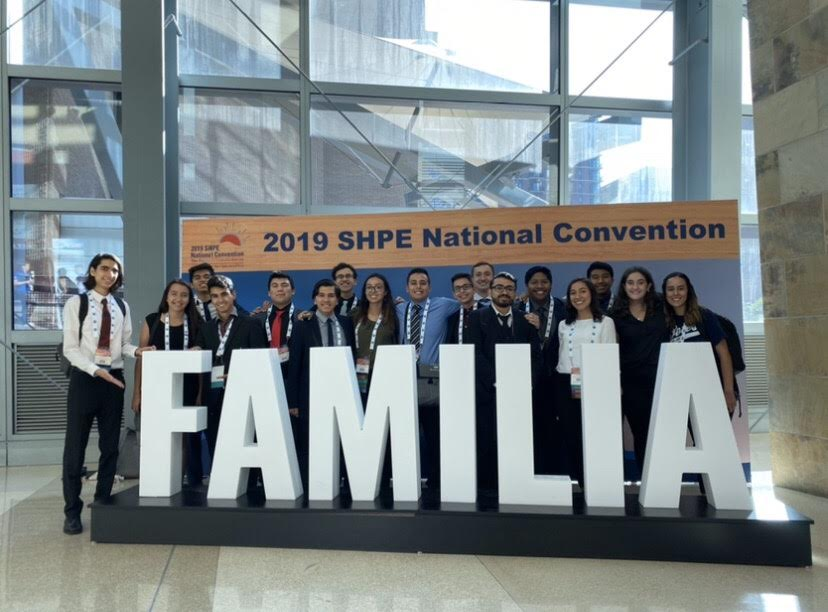 "SOLES members pose at the 2019 SHPE National Convention with a large ""FAMILIA"" emblem."