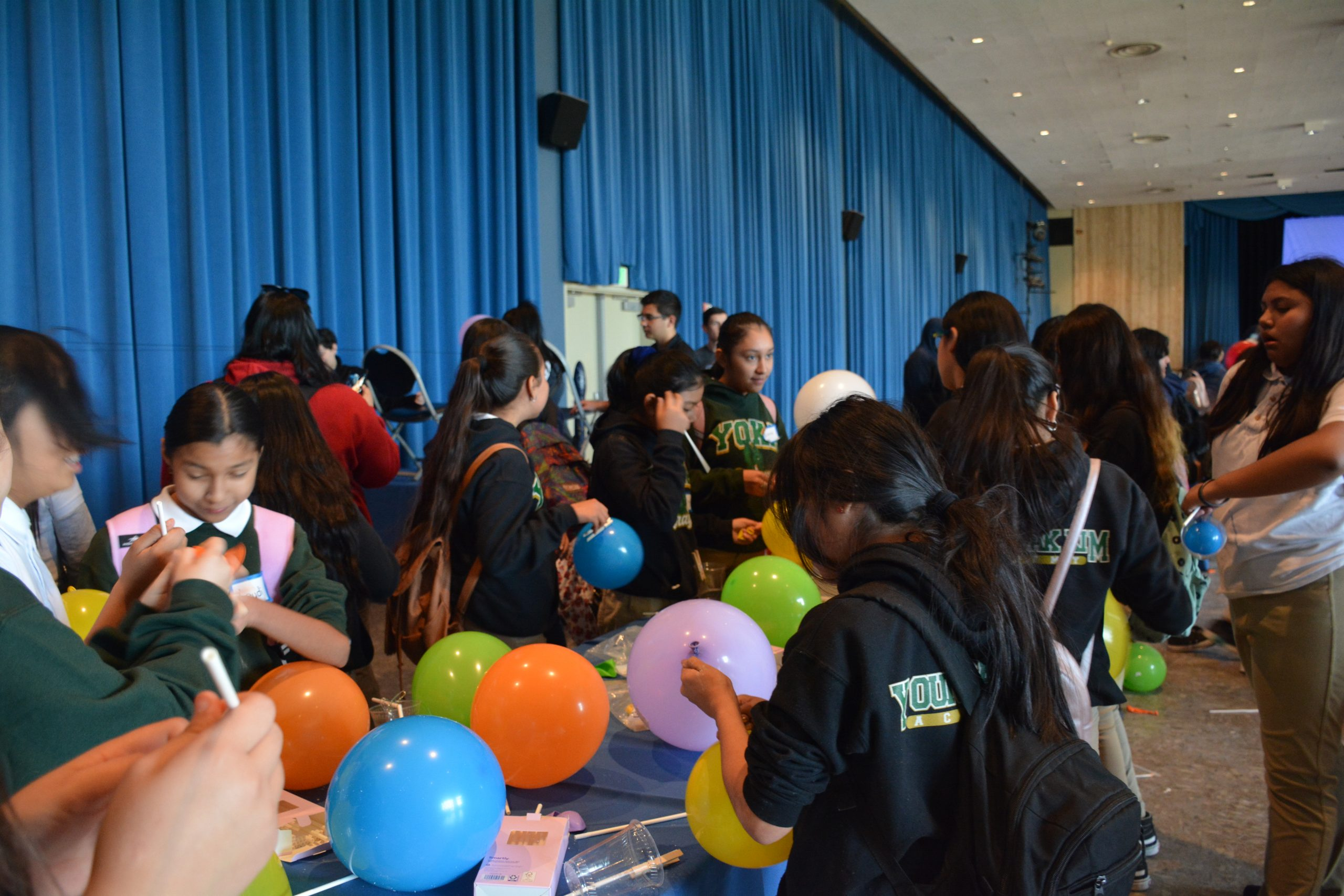 Young students work on an experiment with balloons at Youth Motivation Day